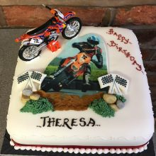 Personalised photo cake featuring a photo of a person on a motocross bike. The cake is square and white.