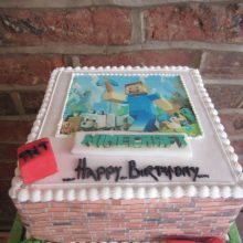 A personalised photo cake with a Minecraft photo on the front. The cake is square in shape and white in colour.