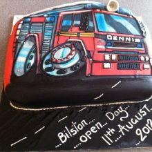 A personalised photo cake with a photo of a fire engine on the front. The cake is red and 3D icing details.