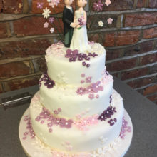 A white wedding cake with pink and purple flowers and icing cake toppers. The cake is on display in a shop in Wolverhampton.