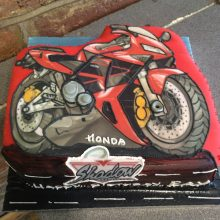 Personalised photo cake featuring a photo of a red Honda motorbike.