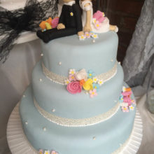 A three tier wedding cake. The cake is light blue in colour with icing roes. The cake also has icing bride and groom on top.