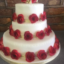 A three tiered wedding cake. The cake is white with red icing roses around every layer.