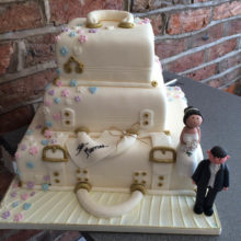 A three tiered wedding cake with each layer resembling a suitcase. The wedding cake includes a icing bride and groom.