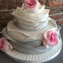 Two tiered wedding cake resembling a rose. The cake is grey with pink roses. Cake on display at a cake shop in Wolverhampton.