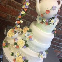 4 Tiered wedding cake with a icing teapot on top. The cake also has a icing teacup and flowers.