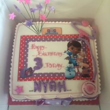 A personalised photo cake for a three year old child. The cake has character photos and is pink and purple.