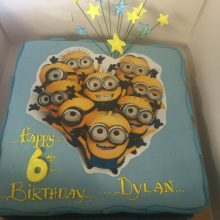 A personalised photo cake. The cake is square in shape and blue. The cake has a photo of Minions on the front.