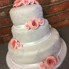 Three tier wedding cake with pink icing roses. The cake is on display in a cake shop in Wolverhampton.