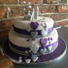 Two tiered wedding cake with purple and silver icing hearts.