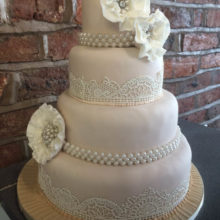 A wedding cake decorated with icing lace and flowers.