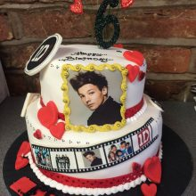 A personalised photo cake featuring a photo of One Direction. The cake is two tired, white with icing hearts.