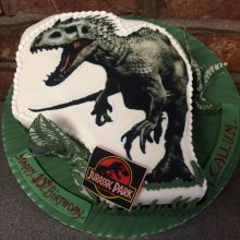 Personalised photo cake featuring a photo of a dinosaur. The cake is white and includes Jurassic Part icing stickers.