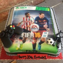 A personalised photo cake with a photo of a Fifa game on the front. The cake is square in shape and has decorative icing toppers.
