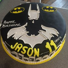 A personalised photo cake with a photo of Batman on the front. The cake is circular in shape and black in colour.