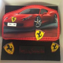 A personalised photo cake red in colour with a photo of a Ferrari on the front.