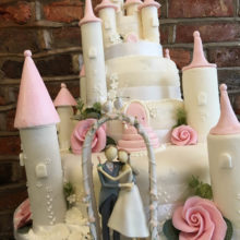 A wedding cake shaped like a castle with two icing figures in front. The cake is on display in a cake shop in Wolverhampton.