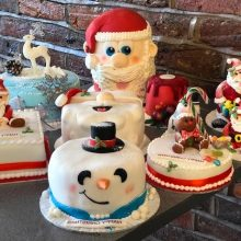A selection of bespoke Christmas cakes sitting on a table.