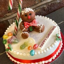 A bespoke cake, round and white in colour. The cake has jelly beans on top and a ginger bread man made out of icing.