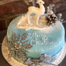 A bespoke cake, the cake is round and blue in colour. The cake says merry Christmas and has a icing reindeer on top.