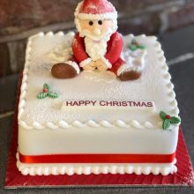 A bespoke cake, square in shape with a Santa figure sat on top made out of icing sugar.