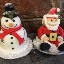 Two bespoke cakes. One looks like a Santa and the other like a snowman.