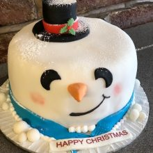 A bespoke cake made to look like a snowman's head. The cake has been dusted with icing sugar to look like snow.