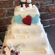 A bespoke three layered cake. The cake is white with two snowmen on the top.